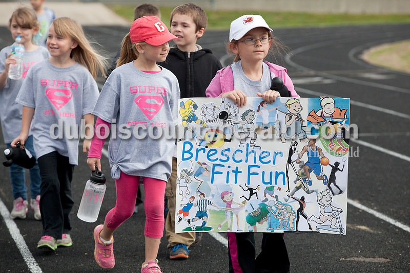 Rachel Mummey/The Herald<br /> First-graders Addison Simmers carried her class's poster as they entered the track during Fifth Street Elementary School's fourth annual Whiskers Walk at Jerry Brewer Alumni Stadium on Friday. The event encouraged kids in all grades to walk for thirty minutes to raise awareness of childhood obesity and promote health and wellness. Simmers got to carry the banner because it was her birthday.