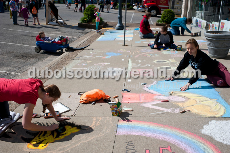 "Carolyn Van Houten/The Herald<br /> Megan Stenftenagel of Jasper, 19, right, drew a woman in the rain during the 11th Annual Chalk Walk Arts Festival in Jasper on Saturday.  The event, which is put on by the Jasper Community Arts Commission, transforms the sidewalks on the Square into huge murals made with colorful chalk.  ""I think it is cool to see what everyone comes up with,"" she said.  ""It inspires art."""