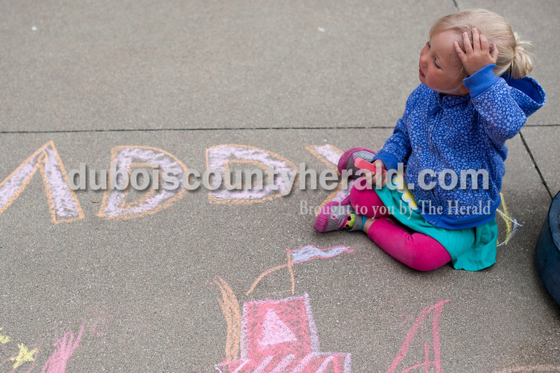 Carolyn Van Houten/The Herald<br /> Addyson Dimmick of Jasper, 2, swept her hair from her face while drawing a pink dolphin during the 11th Annual Chalk Walk Arts Festival in Jasper on Saturday.  The event, which is put on by the Jasper Community Arts Commission, transforms the sidewalks on the Square into huge murals made with colorful chalk.