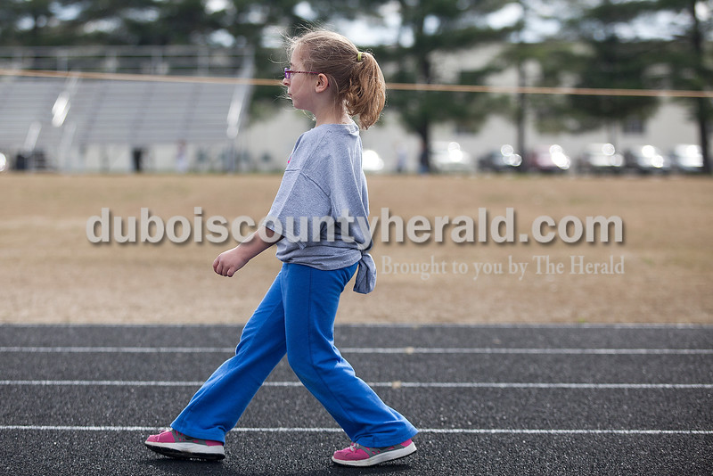 Rachel Mummey/The Herald<br /> First-grader Isabella Steltenpohl walked backwards during Fifth Street Elementary School's fourth annual Whiskers Walk at Jerry Brewer Alumni Stadium on Friday. The event encouraged kids in all grades to walk for thirty minutes to raise awareness of childhood obesity and promote health and wellness.