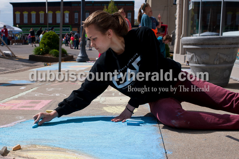 "Carolyn Van Houten/The Herald<br /> Megan Stenftenagel of Jasper, 19, drew a woman in the rain during the 11th Annual Chalk Walk Arts Festival in Jasper on Saturday.  The event, which is put on by the Jasper Community Arts Commission, transforms the sidewalks on the Square into huge murals made with colorful chalk.  ""I think it is cool to see what everyone comes up with,"" she said.  ""It inspires art."""