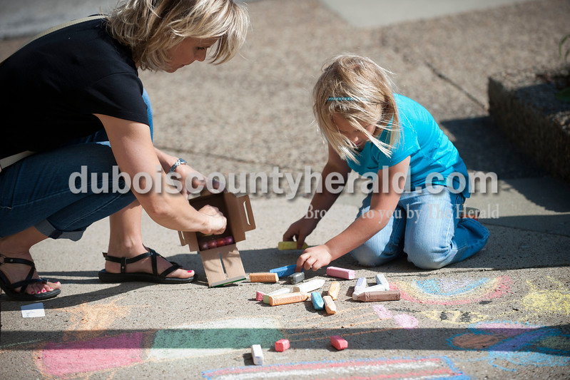 Carolyn Van Houten/The Herald<br /> Emma Small, 6, put chalk away with her mother Robin Small, both of Ireland, during the 11th Annual Chalk Walk Arts Festival in Jasper on Saturday.  The event, which is put on by the Jasper Community Arts Commission, transforms the sidewalks on the Square into huge murals made with colorful chalk.