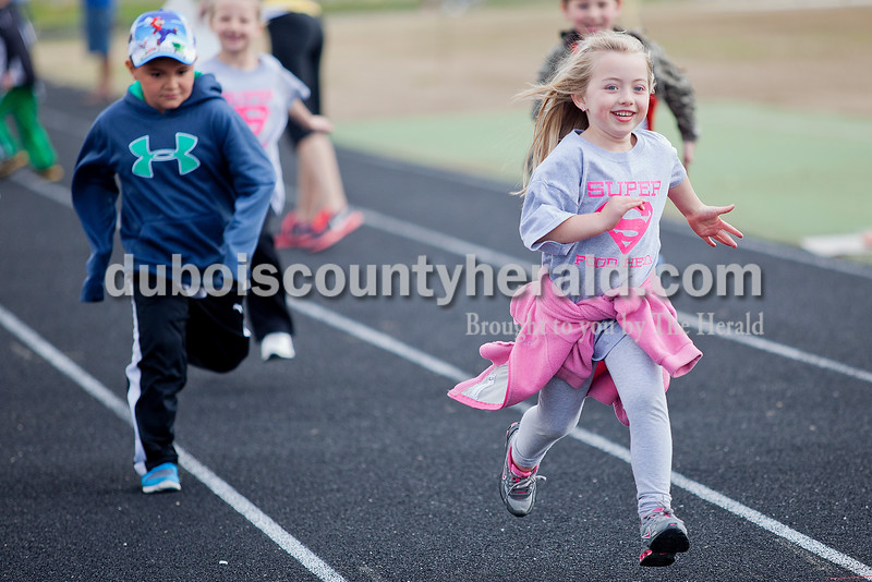 Rachel Mummey/The Herald<br /> Kindergartners Aaron Escobar, left, and Madyson Hurst sprinted around the track during Fifth Street Elementary School's fourth annual Whiskers Walk at Jerry Brewer Alumni Stadium on Friday. The event encouraged kids in all grades to walk for thirty minutes to raise awareness of childhood obesity and promote health and wellness.