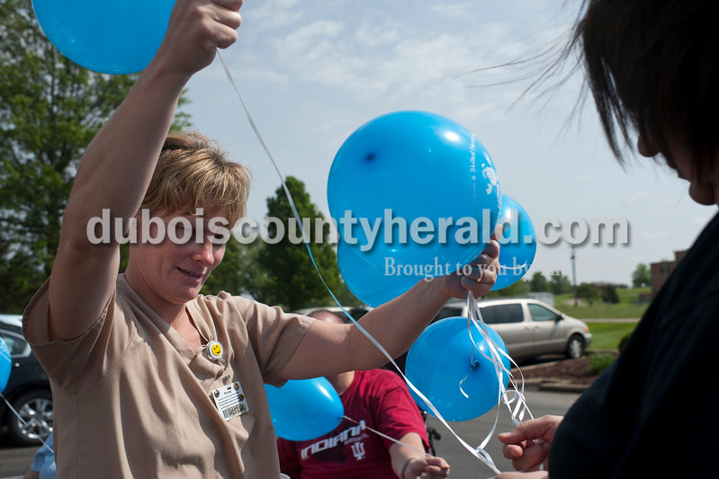 """Carolyn Van Houten/The Herald<br /> Angie Hachmeister, a certified nursing assistant from Huntingburg, helped detangle balloons at the Waters of Huntingburg on Monday.  Residents launched balloons to kick off National Nursing Home Week.  """"If the balloons are found, they have a card with the resident's name and our address, so that the balloon can be mailed back to us with a note,"""" Activities Director Lindsey Burger of Huntingburg said.  """"One year we got balloons back from as far as Kentucky."""""""