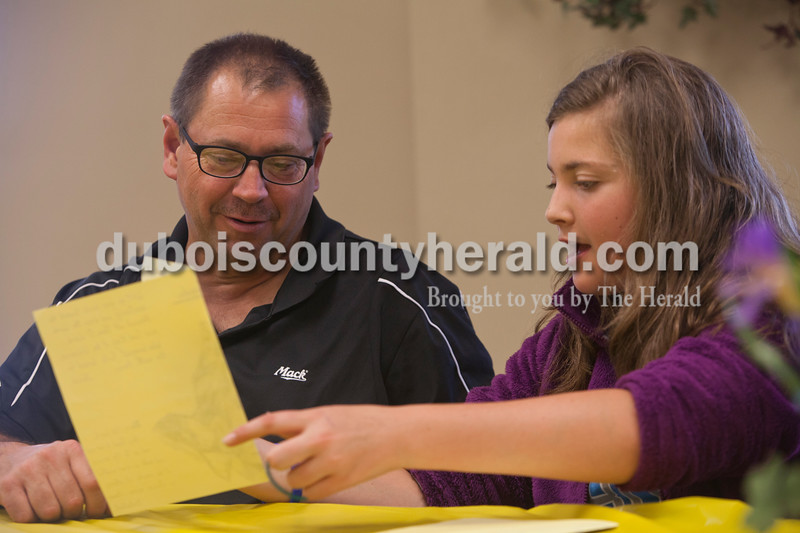Randy Neukam, left, helped his daughter, Taylor Neukam, 12, both of Dubois, practice her presentation about how she used $5 to make a difference. They were at a pot luck dinner on Saturday evening at St. Celestine Church when kids from the St. Celestine and St. Raphael Catholic Cluster Parish  shared what they did with the $5 that was given to them at the beginning of Lent. They were asked to make a difference with the money and share what God taught them. Taylor gathered her guitar teacher and some other local musicians who played a concert at Dubois Middle School. She used the $5 to provided free cookies at the event and asked for money or canned food donations. A total of $454.11was raised, $200.00 and the canned food was given to the food bank and Taylor gave the rest of the money to locals serving in the military. Heather Rousseau/The Herald