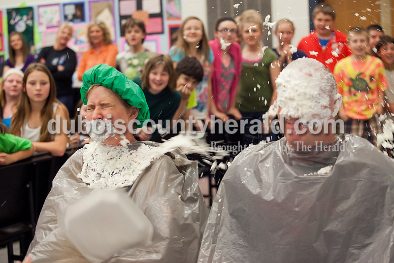Rachel Mummey/The Herald<br /> Seventh-grade Language Arts teacher Linda Schmitt and Principal Ryan Case received pies in their faces between acts during the the talent show at Dubois Middle School on Friday. Students raised over $600 for their Robotics Club by buying one-dollar tickets to see their teachers get pied.