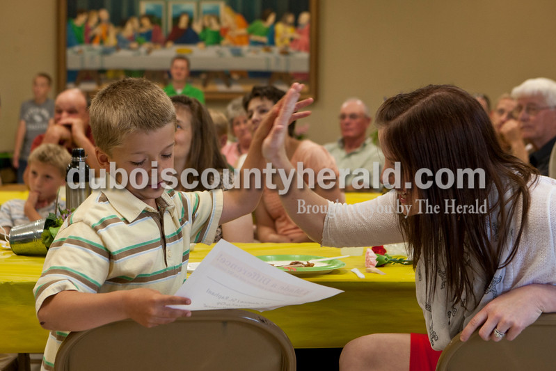 """Nigel Tretter, 7, looked at his """"I made a difference"""" award as his mom, Kelly Tretter, gave him a high-five, both are of Celestine. They were at a pot luck dinner on Saturday evening at St. Celestine Church when kids from the St. Celestine and St. Raphael Catholic Cluster Parish  shared how they made a difference with the $5 that was given to them at the beginning of Lent. Nigel and his sister, Emma bought cookie dough mix with their $5 and had a bake sale. They raised $130 and gave it to their friend, Jeff Huls of Dubois, who lost his home in a fire. Heather Rousseau/The Herald"""