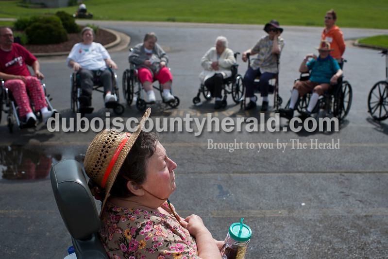 """Carolyn Van Houten/The Herald<br /> Julia Alvey closed her eyes after reciting the National Anthem with her fellow residents at the Waters of Huntingburg on Monday.  Residents sang """"You are my Sunshine"""" after they launched balloons to kick off National Nursing Home Week.  Alvey has been singing regularly for 62 years.  """"They are my family"""" Activities Director Lindsey Burger of Huntingburg said of the residents.  """"I love every single one of them."""""""