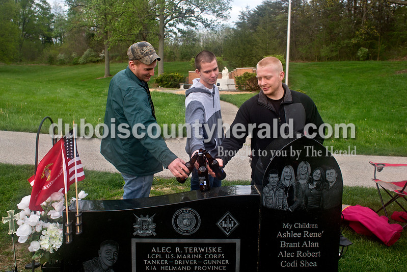 Dave Weatherwax/The Herald<br /> Tyler Lampert of Dubois, left, Logan Borden of Jasper and Logan Ingle of Dubois toasted to their high school buddy and fallen Marine Lance Cpl. Alec Terwiske of Dubois on May 1 in St. Celestine Cemetery in Celestine. The three friends said they and other friends will from time to time gather at Terwiske's grave site, sit in lawn chairs and just spend time visiting their buddy.