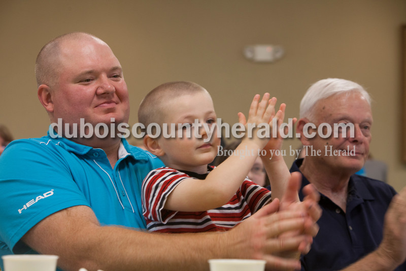 Stan Goodman with his son, Isaiah Goodman, 3, both of Celestine clapped for  kids from the St. Celestine and St. Raphael Catholic Cluster Parish after they shared what they did with the $5 that was given to them at the beginning of Lent. They were asked to make a difference with the money and share what God taught them. Heather Rousseau/The Herald