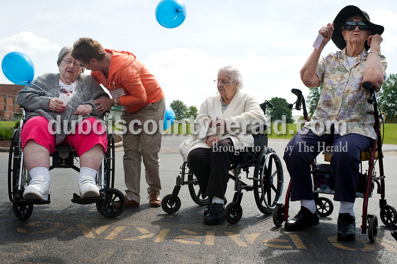 """Carolyn Van Houten/The Herald<br /> Bertha Buechlin, left, spoke with Activities Assistant Vicki Houchin of Winslow while Mary Heidorn and Evalene Hall waited to release their balloons at the Waters of Huntingburg on Monday.  Residents launched balloons to kick off National Nursing Home Week.  """"If the balloons are found, they have a card with the resident's name and our address, so that the balloon can be mailed back to us with a note,"""" Activities Director Lindsey Burger of Huntingburg said.  """"One year we got balloons back from as far as Kentucky."""""""