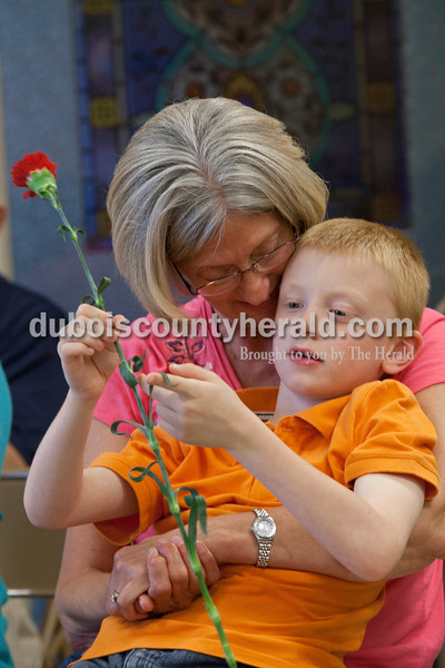Andy Merkley, 6, sat with his grandma, Patty Englert, both of Dubois while holding the flower that was given to her during a Mother's Day Mass. They were a pot luck dinner on Saturday evening at St. Celestine Church. The kids from the St. Celestine and St. Raphael Catholic Cluster Parish shared what they did with the $5 that was given to them at the beginning of Lent. They were asked to make a difference with the money and share what God taught them. Heather Rousseau/The Herald