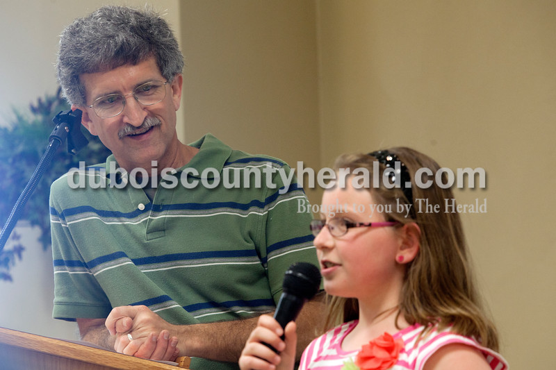 Kendall Buechler, 8, of Celestine shared how she made a difference with $5 as Deacon Mike Seiberts listened during a pot luck dinner on Saturday evening at St. Celestine Church. The kids from the St. Celestine and St. Raphael Catholic Cluster Parish shared what they did with the $5 that was given to them at the beginning of Lent. They were asked to make a difference with the money and share what God taught them. Heather Rousseau/The Herald