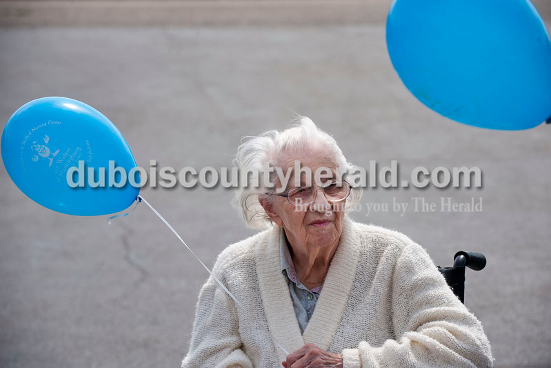 """Carolyn Van Houten/The Herald<br /> Mary Heidorn held onto a balloon outside the Waters of Huntingburg on Monday.  Residents launched balloons to kick off National Nursing Home Week.  """"If the balloons are found, they have a card with the resident's name and our address, so that the balloon can be mailed back to us with a note,"""" Activities Director Lindsey Burger of Huntingburg said.  """"One year we got balloons back from as far as Kentucky."""""""
