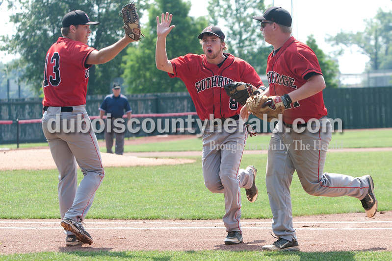 The Raiders' Jacob Brewer, left ,  Connor Craig and Chad Meyer exchanged high-fives after retiring the side during the Class 3A sectional game at League Stadium in Huntingburg on Saturday.  The Raiders defeated the Wildcats 4-1. Heather Rousseau/The Herald