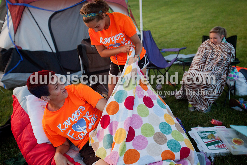 Emily Nord of Ferdinand, 15, second from left, tucked in teammate Grant Winkler of Ferdinand, 16, as they and Kennedy Rainey of Ferdinand, 17, right, took a break from walking laps in the early morning hours at Relay for Life of Dubois County on Saturday at Jasper Middle School. Rachel Mummey/The Herald