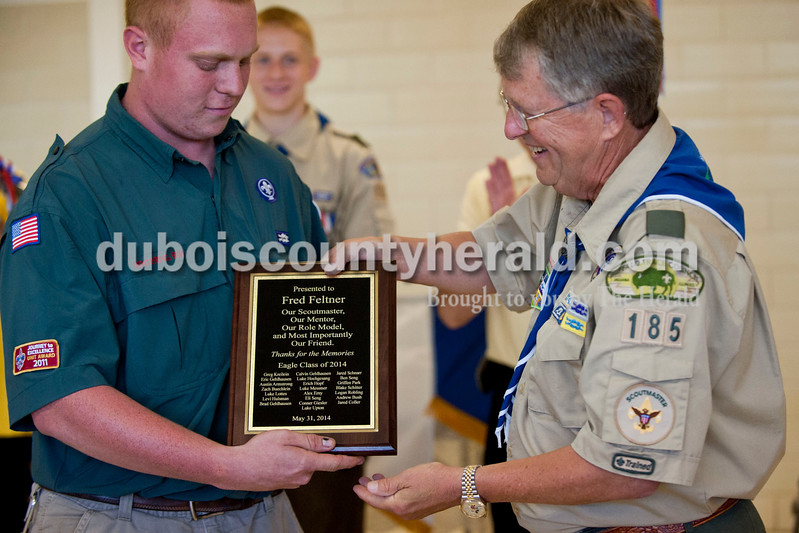 "Carolyn Van Houten/The Herald<br /> Greg Kreilein of Jasper, 18, presented his Eagle Scout Troop 185 leader Fred Feltner with a plaque during a court of honor at St. Mary's Church in Ireland on Saturday.  Twenty-two seniors from his troop, all of whom are Eagle Scouts, surprised him with the plaque.  ""He has helped shape my character,"" 18-year-old Alex Erny of Jasper, who is one of the senior Eagle Scouts, said."