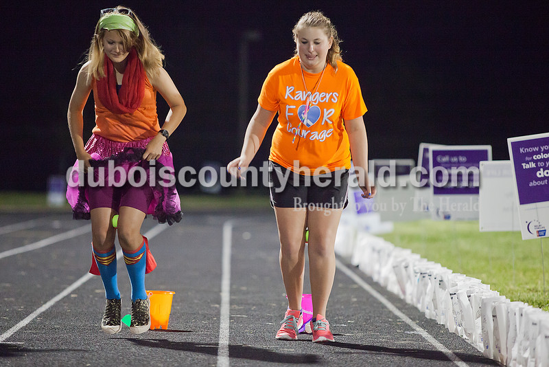 "Brook Altmann, left, and Morgan Wessel, both 16 and of Ferdinand, squeezed tennis balls between their legs while playing a relay game called ""Deliver the Fool's Gold"" during the early morning hours at Relay for Life of Dubois County on Saturday at Jasper Middle School. Rachel Mummey/The Herald"