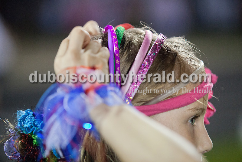 Emma Woolsey of Holland, 9, fixed her hair for the crazy hair lap competition at Relay for Life of Dubois County on Friday at Jasper Middle School. Woolsey had nine headbands to complete her look. Rachel Mummey/The Herald