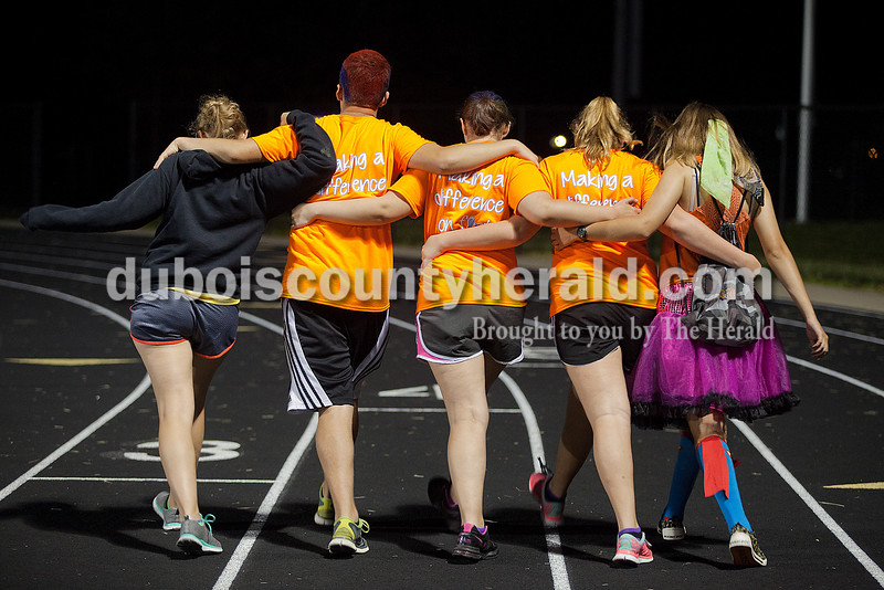 Sam Wendholt of Brezville, 16, left, Grant Winkler of Ferdinand, 16, Diane Durcholz of Saint Anthony, 16, Morgan Wessel of Ferdinand, 16, and Brook Altmann of Ferdinand, 16, tried walking in sync with each other while making laps during the early morning hours of Relay for Life of Dubois County on Saturday at Jasper Middle School. Rachel Mummey/The Herald