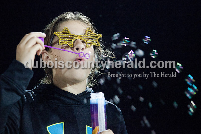 Darby Patton of Jasper, 11, passed some idle time by blowing bubbles at Relay for Life of Dubois County on Saturday at Jasper Middle School. Rachel Mummey/The Herald