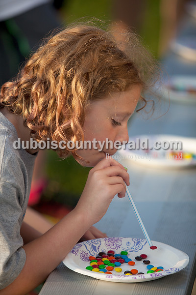 "Kelli Horn of Huntingburg, 10, sucked M&Ms to a straw during a game called ""The Many Colors of the Rainbow"" during Relay for Life of Dubois County on Saturday at Jasper Middle School. Rachel Mummey/The Herald"