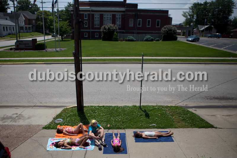 Melissa Macias, 9, front left, Jazmin Leon, 8, Meredith Hein, 12, center,  Ariana Leon, 4 and Yuliana Leon, 6, right, all of huntingburg dried off in the sun after playing in the water with a hose in the Leon sisters' yard at 5th and Main on Sunday. The girls were surprised to hear the temperature was in the high 80's when Hein looked it up on her phone, they thought it felt much hotter outside.