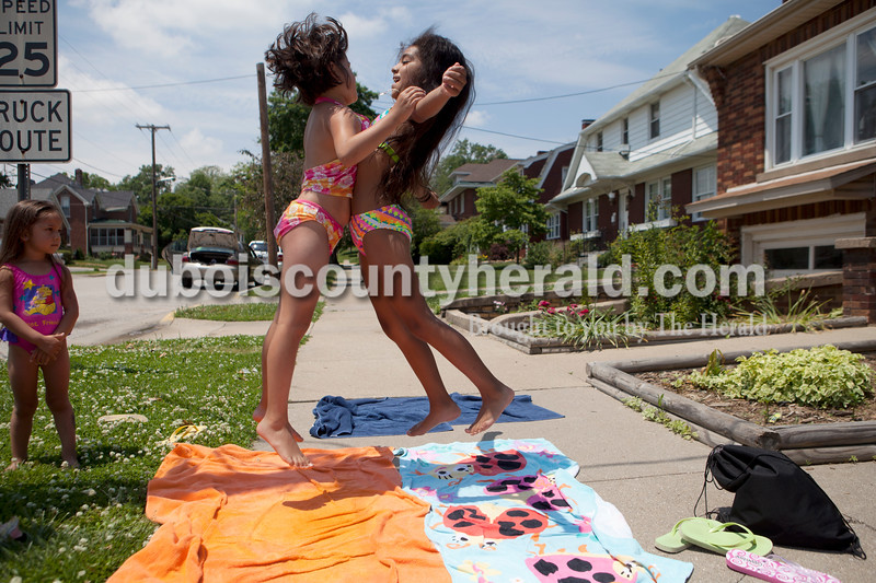 Ariana Leon, 4, left, watched as her sister chest-bumped their friend, Melissa Macias, 9, all of Huntingburg while hanging out in the sun to dry off after playing in the water with a hose in the Leon sisters' yard at 5th and Main on Sunday. The girls were surprised to hear the temperature was in the high 80's when Leon looked it up on her phone, they thought it felt much hotter outside.