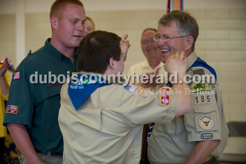 "Carolyn Van Houten/The Herald<br /> Greg Kreilein of Jasper, 18, left, watched as Zach Beckman of Jasper, 21, hugged Eagle Scout Troop 185 leader Fred Feltner after Feltner was presented with a plaque during a court of honor at St. Mary's Church in Ireland on Saturday.  Twenty-two seniors from his troop, all of whom are Eagle Scouts, surprised him with the plaque.  ""He has helped shape my character,"" 18-year-old Alex Erny of Jasper, who is one of the senior Eagle Scouts, said."