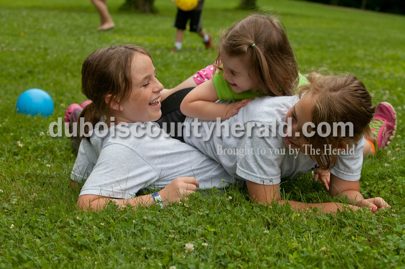 Heather Rousseau/The Herald<br /> Merin Buck, 9, left, and her sisters Maci, 11, and Maggie, 3, all of Jasper, laughed after tumbling down to the grass while playing ball at the Arnold F. Habig Community Center on Monday during Kamp 4 Kids put on by the Jasper Park and Recreation Department. The cost is $35 a week and takes place until the end of July. In addition to indoor and outdoor activities, the group  goes to the city pool once a week. Though the program is for younger children, Merin and Maci go as volunteers because they want to spend time with their younger sister.