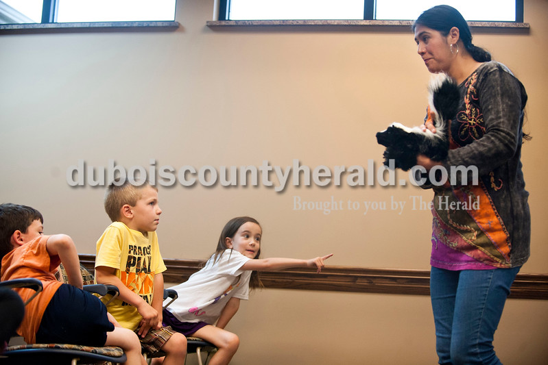 Carolyn Van Houten/The Herald<br /> Ale Klawitter of Dubois showed Ty Betz of Celestine, 6, left, Bryce Reuber of Celestine, 5, and Madeline Zipp of Ferdinand, 6, what warnings skunks give before they emit their spray during the Animals of Indiana Puppet Show at the Dubois Library on Wednesday.  Klawitter volunteered to teach the 15 children attending interesting facts about each mammal, bird, marsupial and insect native to the area.  She used some of her more than 80 realistic puppets in the show, some of which blinked and moved as the real animals would.