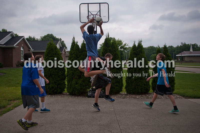Carolyn Van Houten/The Herald<br /> Brenton Abbett of Jasper, 15, center, jumped up to shoot the ball, but was fouled by Jake Ruxer, 15, of Jasper, as Brenton's brother Piercen Abbett, 13, left, Josh Ruppert, 13, of Indianapolis, and Quintin Gordon, 14, of Jasper, looked on outside of the Abbett's home in Jasper on Tuesday.  The boys were playing basketball with a soccer ball and were split up on teams according to shirt color--the blue shirts on one team and all of the other colors on the other team.  The boys continued to play despite the pouring rain.