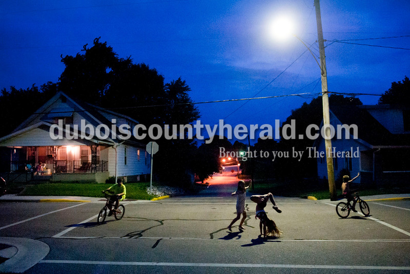 """Carolyn Van Houten/The Herald<br /> Ethan Buckner, 10, left, Jane Franklin, 8, Lexi Brinksneader, 10, and Trey Brinksneader, 7, played under a streetlight during the Brinksneader family's barbecue on Saturday outside their home in Jasper.  Denise Brinksneader, mother to Lexi and Trey, said, """"At least twice a month we like to get friends, family, neighbors and coworkers together for ribs, taters and cornhole.""""  They had at least 20 people over from Dubois and surrounding counties on Saturday.  Afterwards, the local children had a sleepover at the Brinksneader's house."""