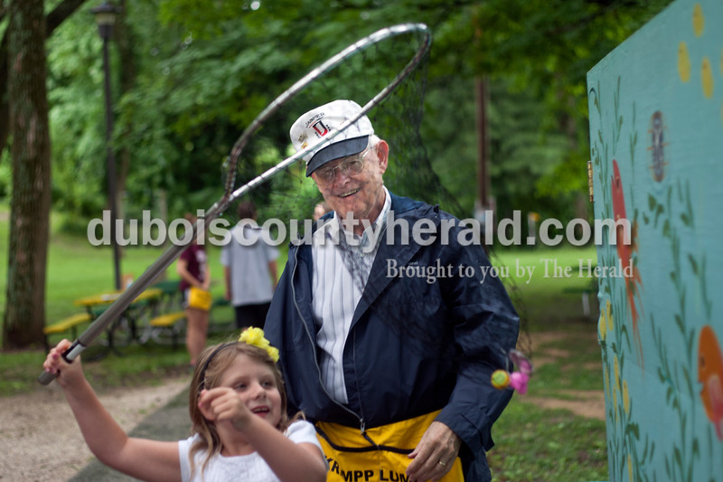 """Heather Rousseau/The Herald<br /> Art Nordhoff smiled as he helped Chloe McCracken, 6, both of Jasper, go fishing for toys in the """"fish-pond"""" during the Kiwanis Kiddie Karnival at Jaycee Parkin in Jasper on Wednesday. Kids caught anything from bubbles to silly face masks, Ring-Pops and  Playdough. Nordhoff was at the first Kiddie Karnival 66 years ago when it was held in Jasper local David Held's back yard. Nordhoff was 8-years old at the time. He now volunteers with the Kiwanis Club."""