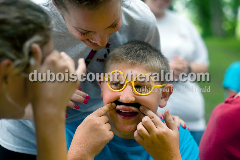 Heather Rousseau/The Herald<br /> Clayton Sander, 10, of Celestine, held onto his fake mustache as Jessica Lehmkuhler, 23, behind, and Morgan Rottet, 18, both of Jasper helped him with the glasses he won during the Kiwanis Kiddie Karnival at Jaycee Park in Jasper on Wednesday. Sanders was there with Camp C.A.R.E. (Campers Are Really Exceptional),  Lehmkuhler and Rottet are on staff.