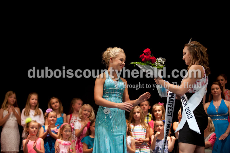 Carolyn Van Houten/The Herald<br /> Sabrina Becher of Ferdinand, 16, received her Miss Heimatfest First Runner-up sash and flowers from the 2013 Miss Heimatfest Shanna Hoffman during the Miss Heimatfest Pageant in the Forest Park Auditorium in Ferdinand on Sunday.  The Little Miss and Little Mister Heimatfest Pageants were held simultaneously.  There were eight Miss Heimatfest contestants who walked on stage in work wear, theme wear and formal wear rounds.  During the last round, each contestant was asked impromptu questions.  The 2014 Miss Heimatfest winner was Shelby Klem of Ferdinand, 18, who was also Miss Photogenic.  The First Runner-up was Sabrina Becher, 16, of Ferdinand.  Tiffany Singer of Ferdinand, 18, won Miss Congeniality.