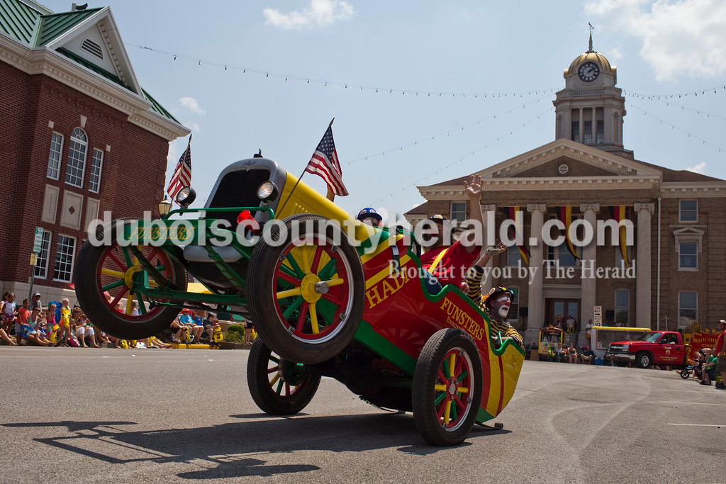 """Wes """"Sniffles"""" Whiteside, center, Chad """"Slug-O"""" Dewton, left, and Kelly """"Juggles"""" Allen, right, all of Evensville, rode their clown car in the Jasper Strassenfest Parade on Sunday. Caitlin O'Hara/The Herald"""