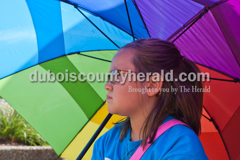 Kenna Brosmer, 9, of Celestine waited under the shade of an umbrella for the parade to start at Jasper Strassenfest on Sunday. Her sister, Ava, 8, was going to be throwing candy.<br /> Caitlin O'Hara/The Herald