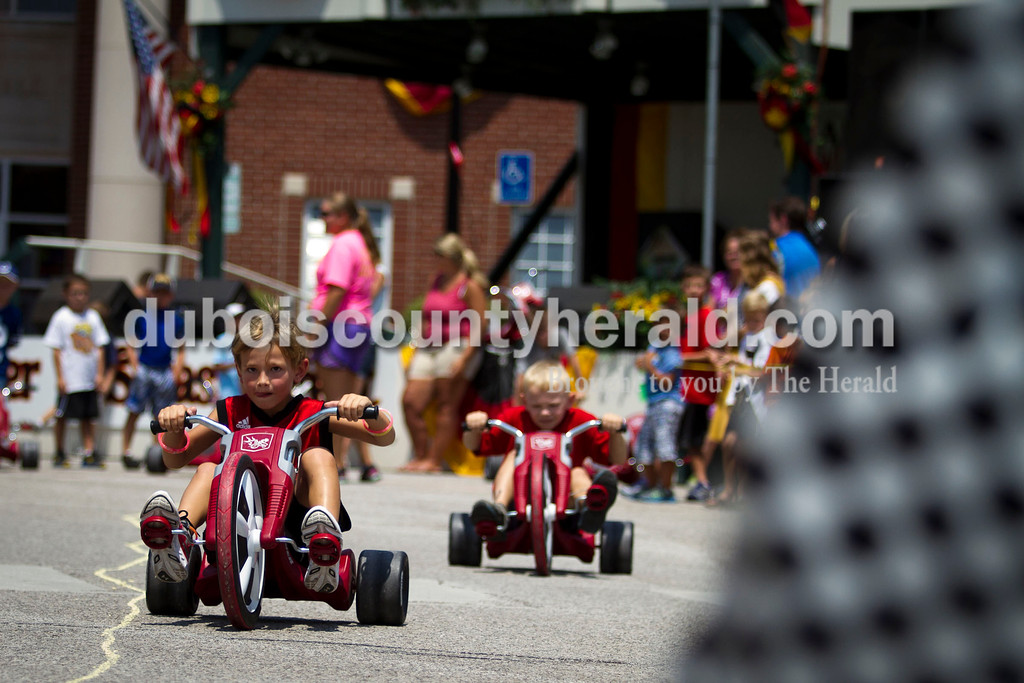 Joel Levy, left, raced Alec Wehr, both 6 and of Jasper, toward the finish line and checkered flag during the big wheel race at the Jasper Strassenfest on Saturday.<br /> Caitlin O'Hara/The Herald