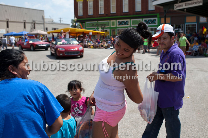Yazmin Torres, 16, laughed after her friend, Maria Rodriguez, left, poured water down her back at the Jasper Strassenfest Parade on Sunday. Rodriguez's husband, Julian Salas, and their children, Julian, 3, and Karina, 4, watched on.<br /> Caitlin O'Hara/The Herald