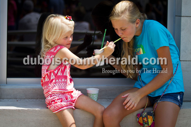 Adalyn Welp, 4, of Jasper, left let her sister, Hanna, 14, try her root beer slushie at the Jasper Strassenfest on Saturday. <br /> Caitlin O'Hara/The Herald