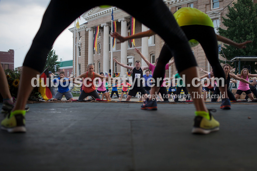 An Insanity Exercise Routine seen through the legs of Fit Together co-owners Jill Wigand, left, and Jamie Jahn, right, both of Jasper, at the Jasper Strassenfest on Saturday.<br /> Caitlin O'Hara/The Herald