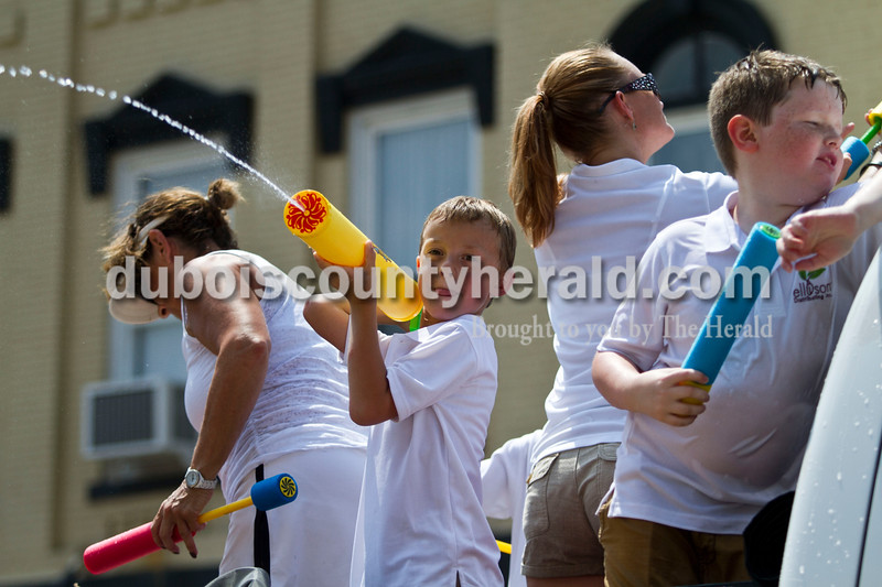 The Ellison Distributing float members sprayed the crowd at the Jasper Strassenfest parade on Sunday.<br /> Caitlin O'Hara/The Herald