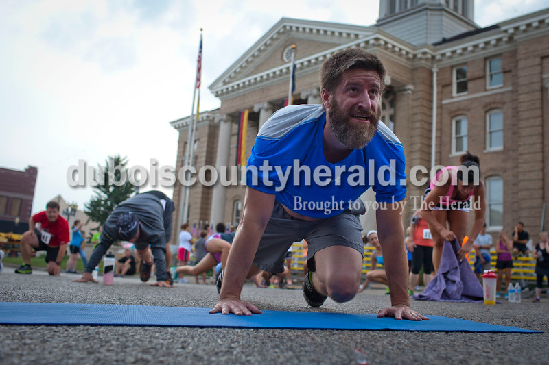 Jason Harris of Jasper stretched after participating in an Insanity Exercise Routine at the Jasper Strassenfest on Saturday.<br /> Caitlin O'Hara/The Herald
