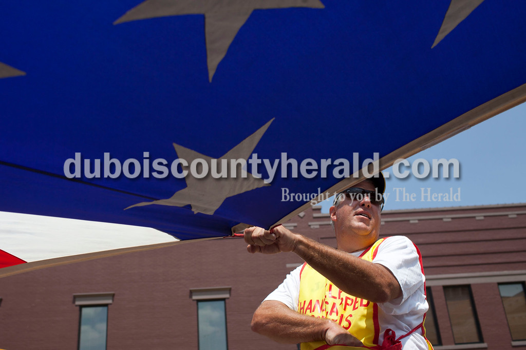 Jeff Theising of Jasper threw candy while toting a huge American flag at the Jasper Strassenfest Parade on Sunday.<br /> Caitlin O'Hara/The Herald
