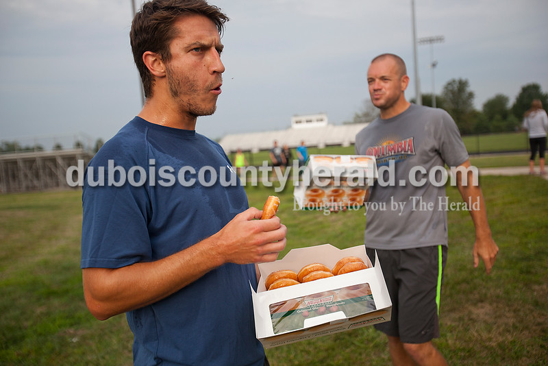 Rachel Mummey/The Herald<br /> The Dubois County Herald sport reporter Joe Jasinski, left, and news editor Jason Recker, both of Jasper, struggled to fishing a dozen donuts during the Don't Sweat It Fitness Krispy Kreme Challenge at Jasper Middle School on Saturday morning. Jasinski successfully ate all twelve donuts and came in first place. All the proceeds went to the Autism Speaks organization.