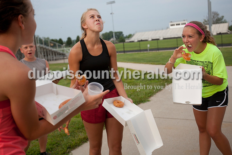 Rachel Mummey/The Herald<br /> Lauren Rennie, 16, left, Madeline Hurst, 17, second from right, Rachael Welsh, 16, all of Jasper, struggled to finish a half-dozen donuts between two one-mile runs during the Don't Sweat It Fitness Krispy Kreme Challenge at Jasper Middle School on Saturday morning. Hurst successfully ate all the donuts and came in first place for the half challenge. All the proceeds went to the Autism Speaks organization.