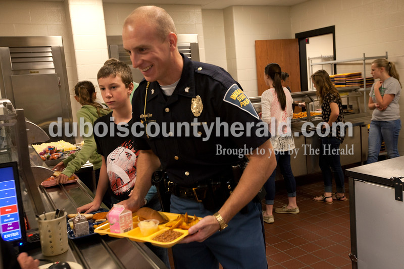 """Heather Rousseau/The Herald<br /> Ind. State Trooper Sgt. Philip Hensley got lunch at the Jasper Middle School cafeteria on Monday after giving a presentation to students about bullying. 8th grader Jade Bartley, behind at left, was there for one of the presentations.  He said what he took away was """"don't waste your time (bullying)."""" Sgt. Hensley ate lunch with the faculty before giving his final and third presentation."""