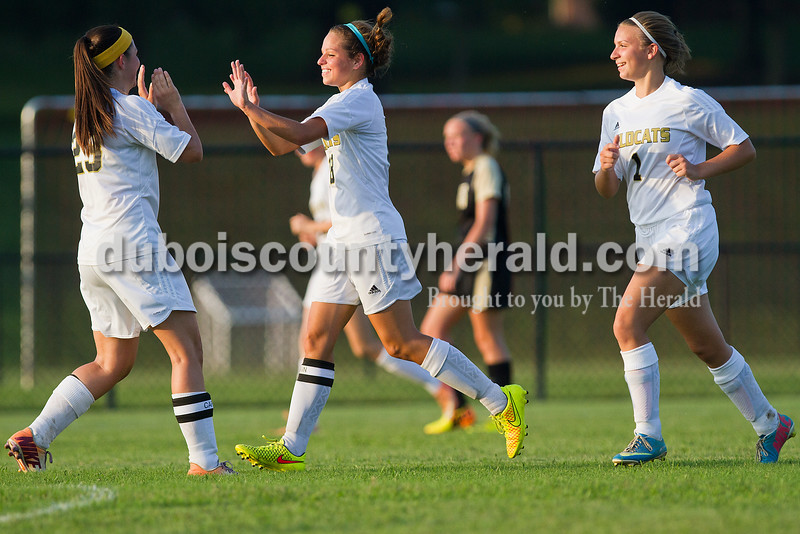Jasper's Elizabeth Day, left, high-fived teammate Brittany Haskins with Sara Carpenter, after scoring a goal during Monday's game against Boonville in Jasper. Rachel Mummey/The Herald