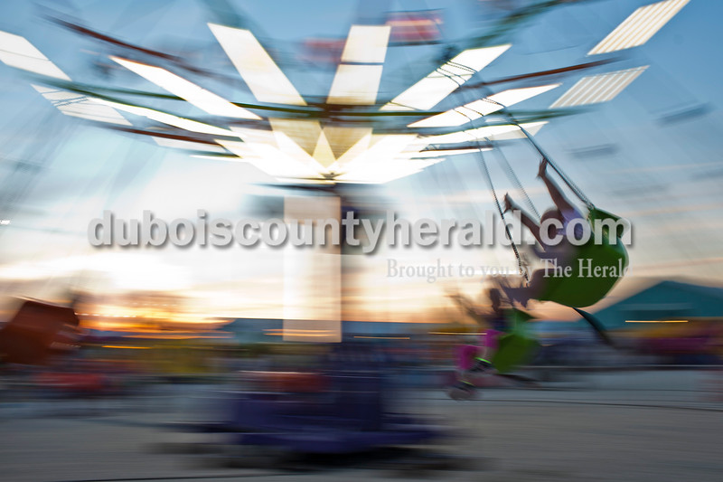 Hailey Pund of St. Anthony, 9, right, rode the swings at the midway at the Dubois County 4-H Fairgrounds.<br /> Caitlin O'Hara/The Herald